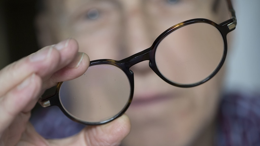 person holding up a pair of spectacles