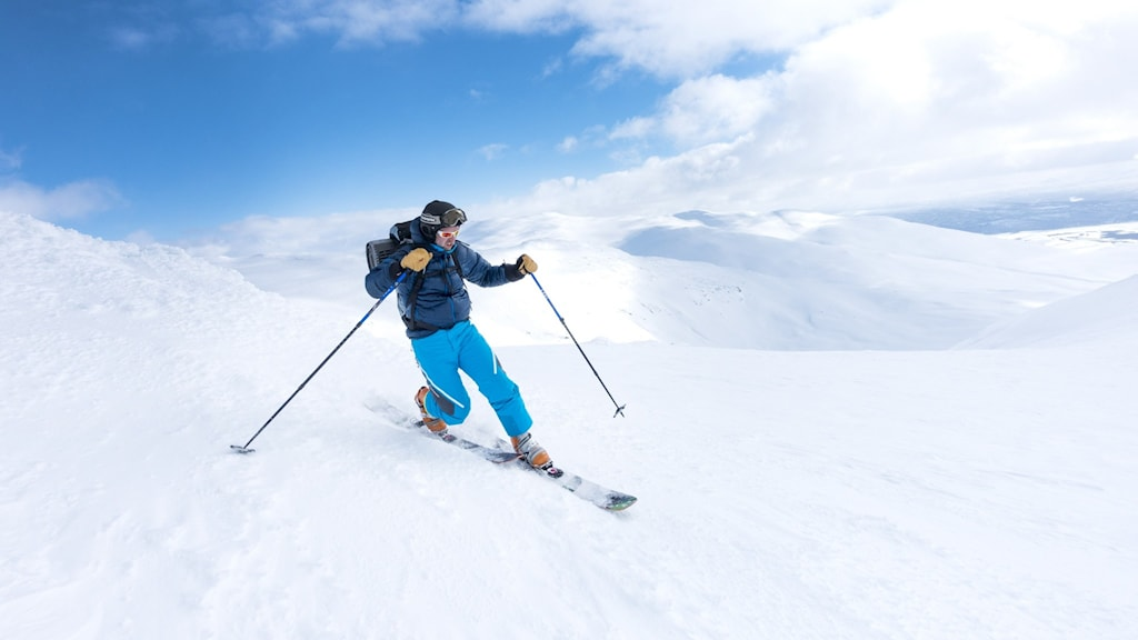 A skier heading down alone on a mountain top.