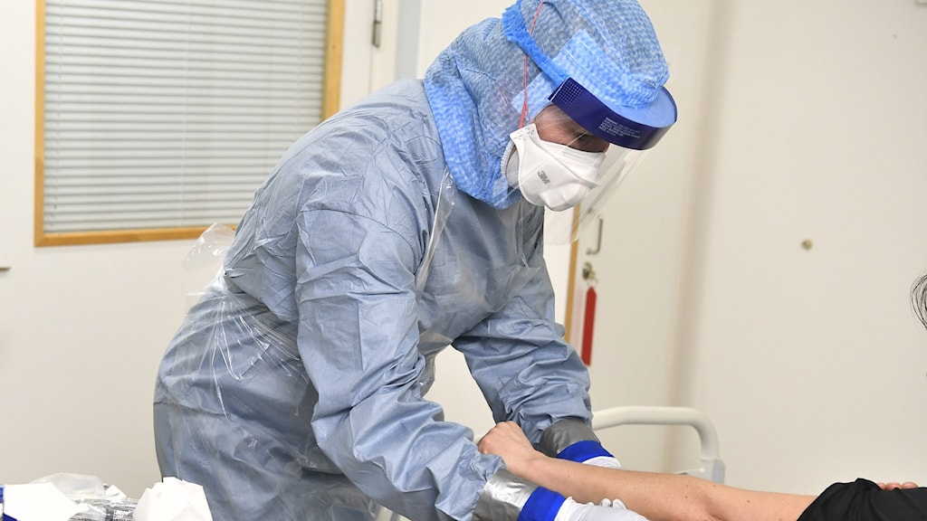 Image of health care staff in full corona protection gear tending to a patient.