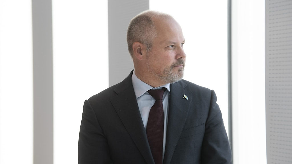 A man in a dark suit against a light background.
