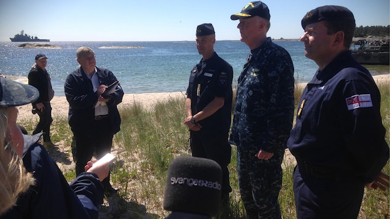 Presenting the Baltops exercise to the media on a beach in the archipelago was the American vice-admiral in charge of Baltops, James Foggo, flanked by Swedish and British rear-admirals, Jens Nykvist and Paddy McAlpine. Photo: Loukas Christodoulou/Sveriges Radio.