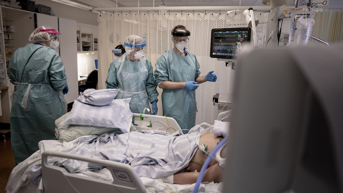 A hospital room with nurses and a patient on a bed.