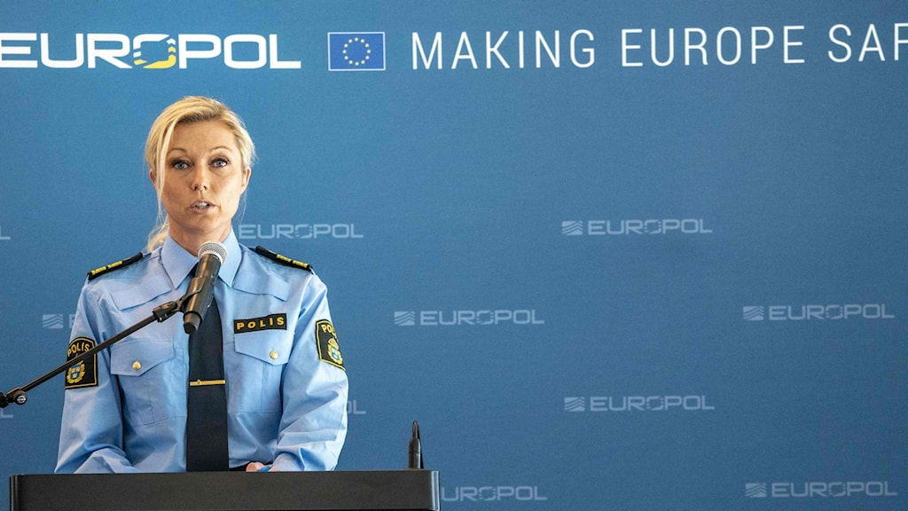 A woman in police uniform at a press conference.