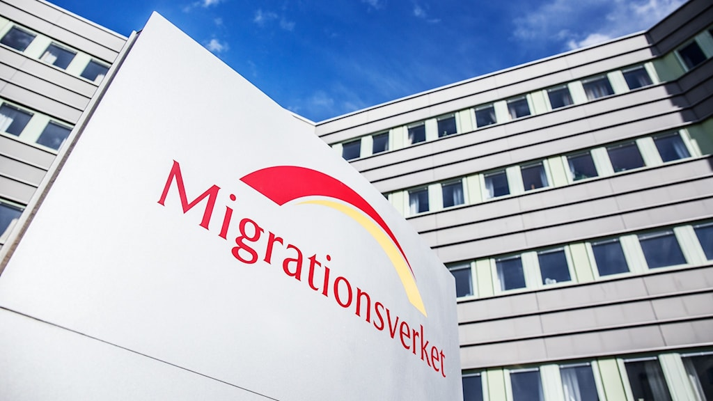 Logo of the Migration Agency in front of a building.