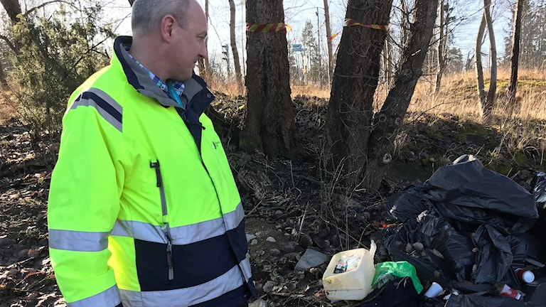 A man in a high-vis vest standing next to a pile of trash in the woods.