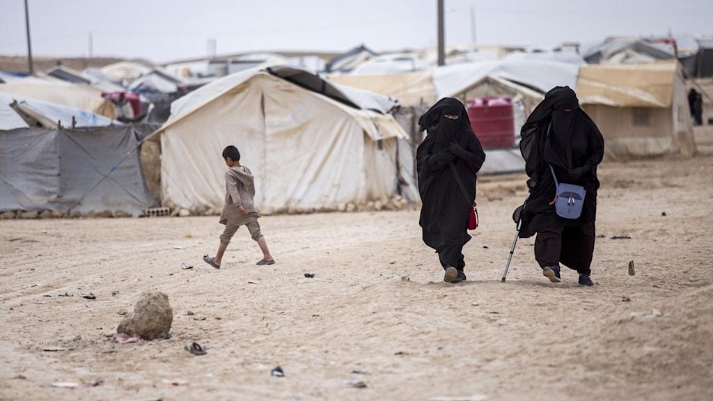 Image of two women in black burkah's walking on a dustry road near a tent camp.