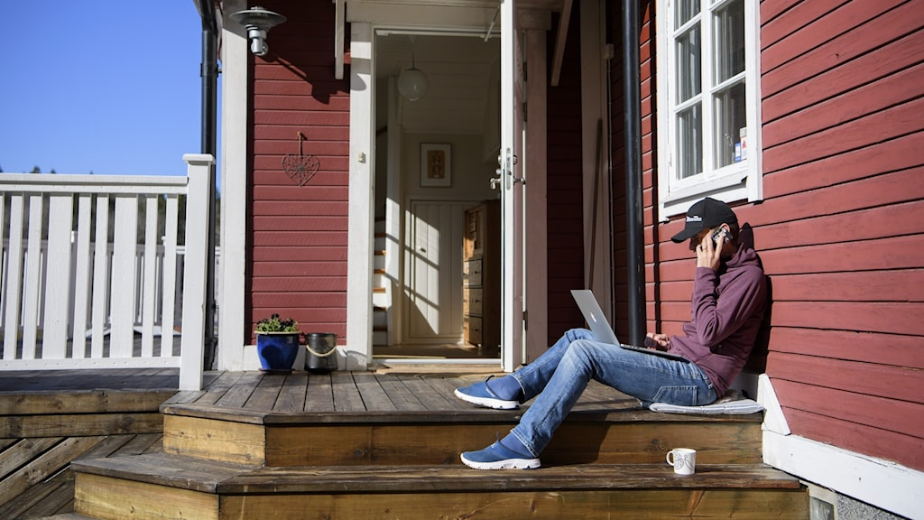 A man sitting on a front porch in the sun talking on a cellphone.