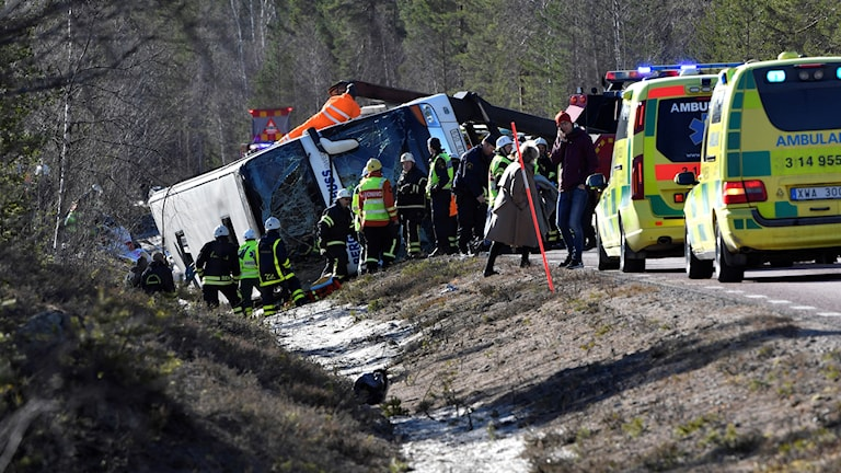 An overturned bus surrounded by rescue workers.