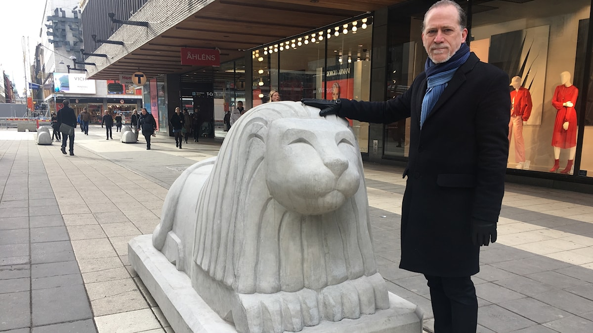 man standing on a pedestrian street, with his hand on a big sculpture of a lion.