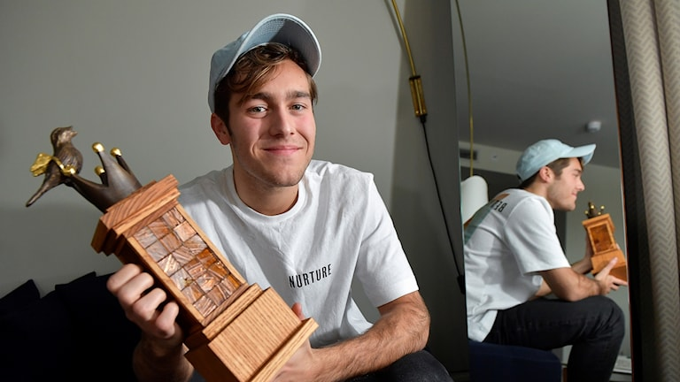 guy holding a trophy and wearing a baseball cap
