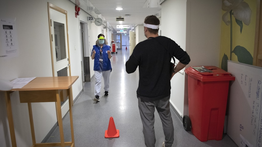 Hallway in hospital with a woman and a man, both wearing protective items.