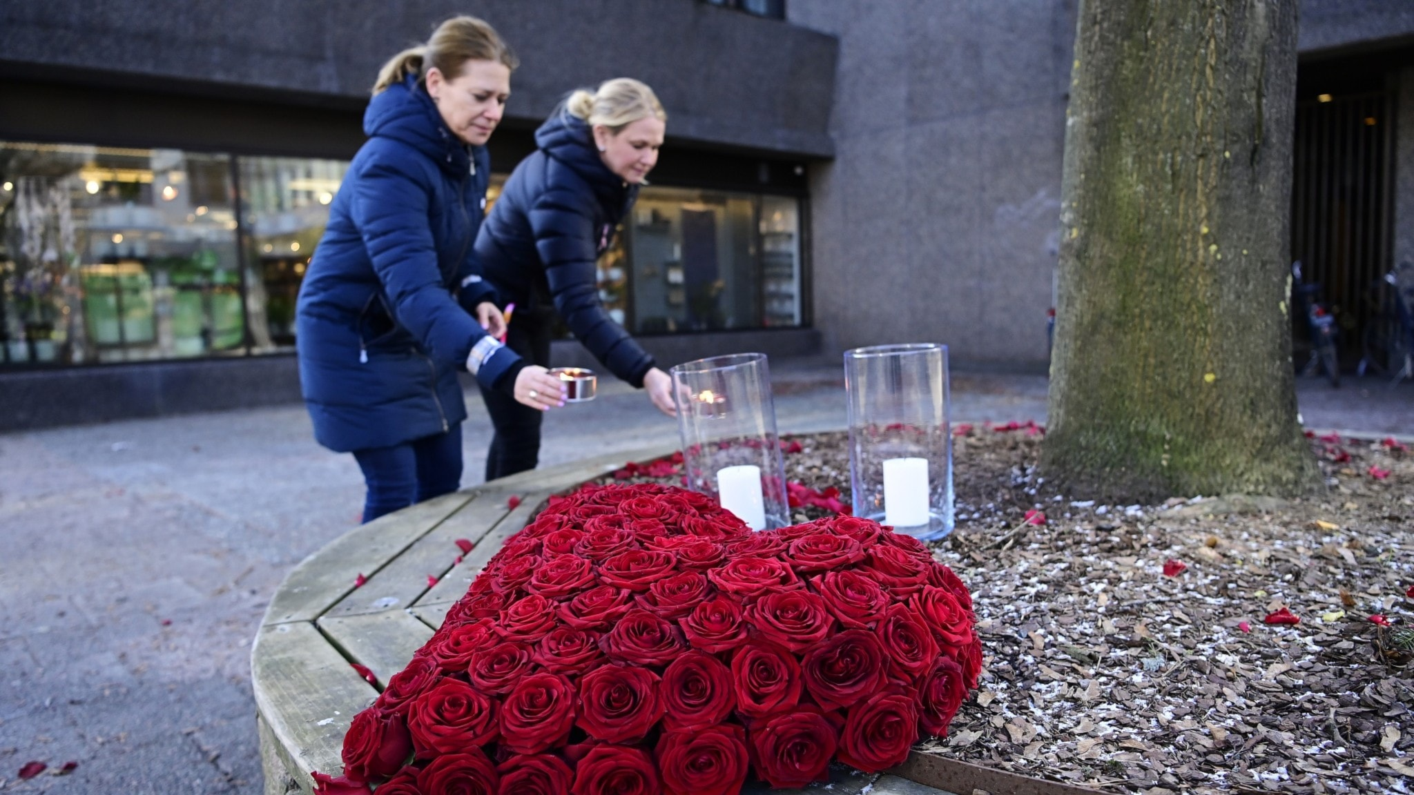 An image of people laying flowers outside.