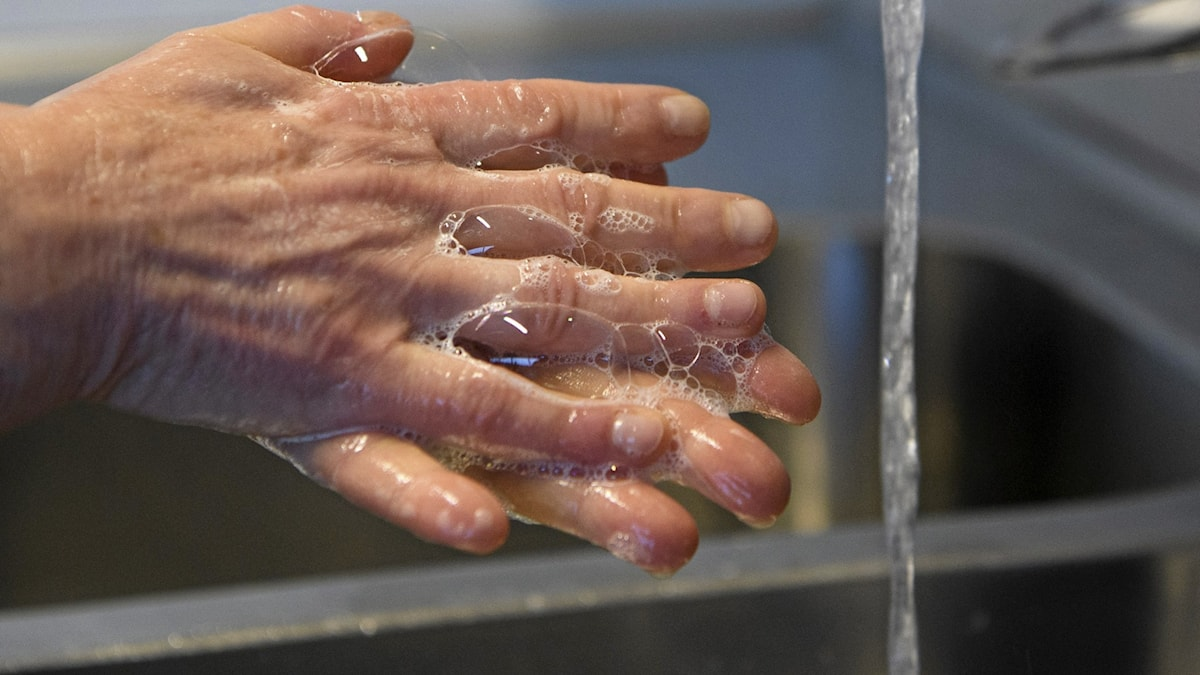 Close-up of a person washing hands.