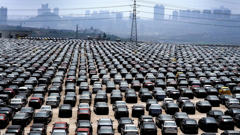 parking lot full of cars with urban skyline in the background