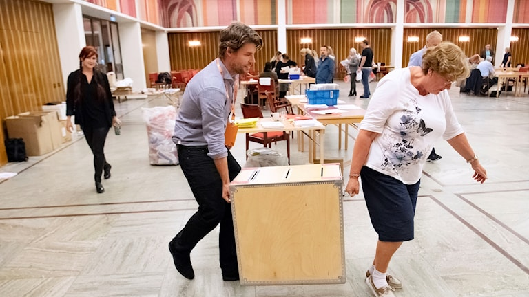 Election workers carry box of votes.