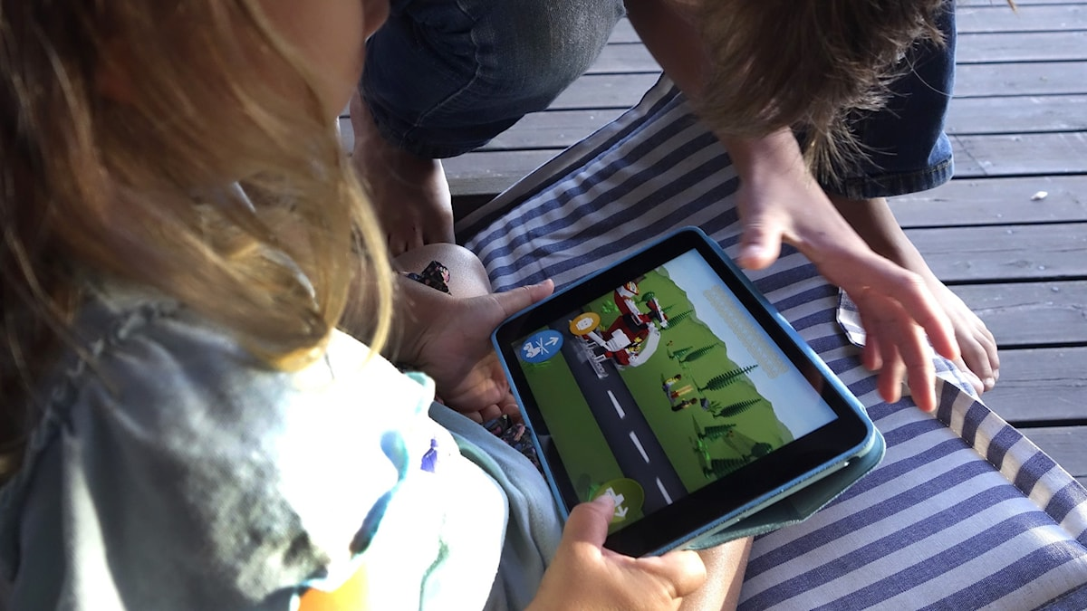 Children holding a tablet.