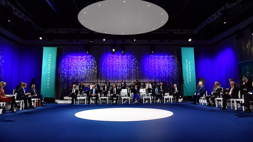 Attendees sitting on chairs on three sides of a stage listening to each other.