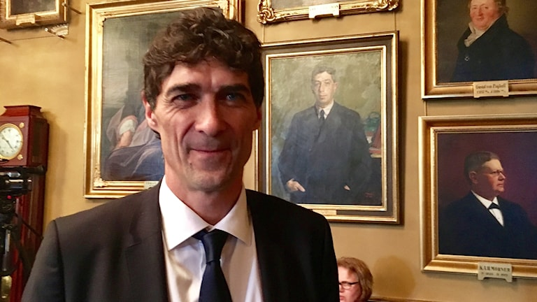 Man in tie and suit in front of several old portraits.
