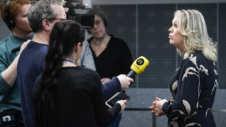 Journalists stretching out microphones to a woman, who answers questions.