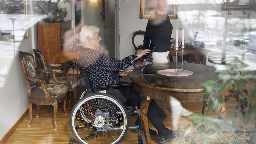 A photo through a window of a woman in a wheelchair at a table.