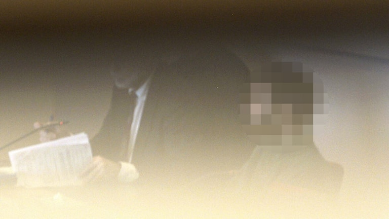 The suspect, with his face obscured, seated next to his lawyer. Photo: Janerik Henriksson / TT.