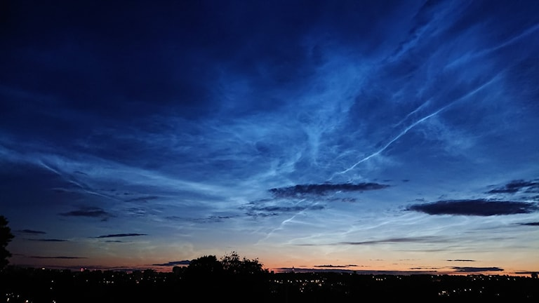 A dark blue twilight sky with bright lines of cloud.