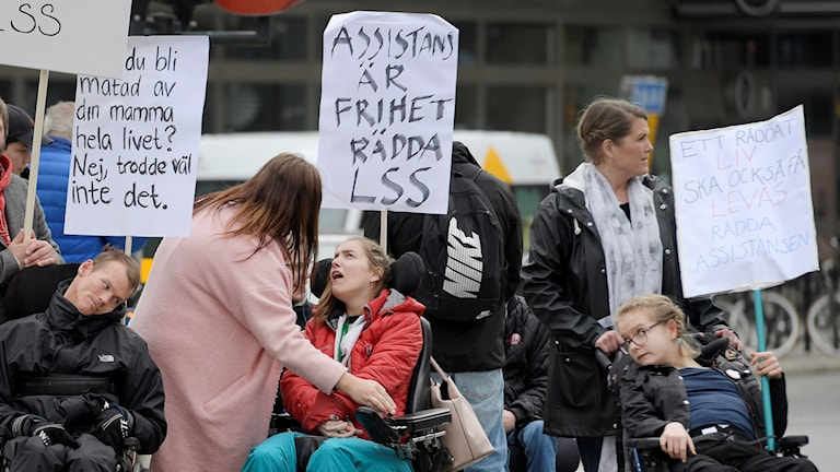 People in wheelchairs and others standing holding placards.