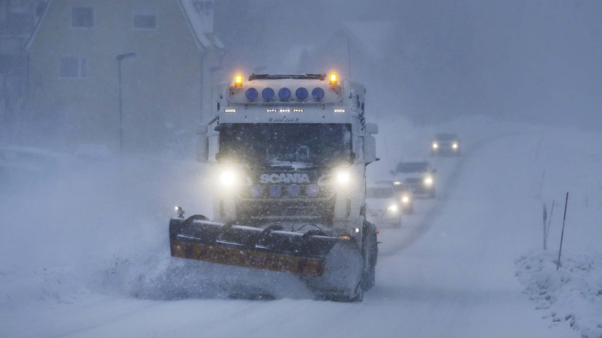 A large snow plough clearing a road with a line of cars behind it.