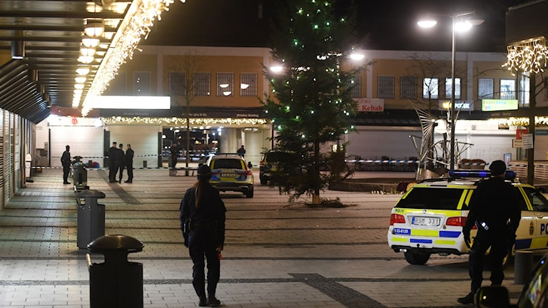Polis car and police officers on a lit-up square after dark.