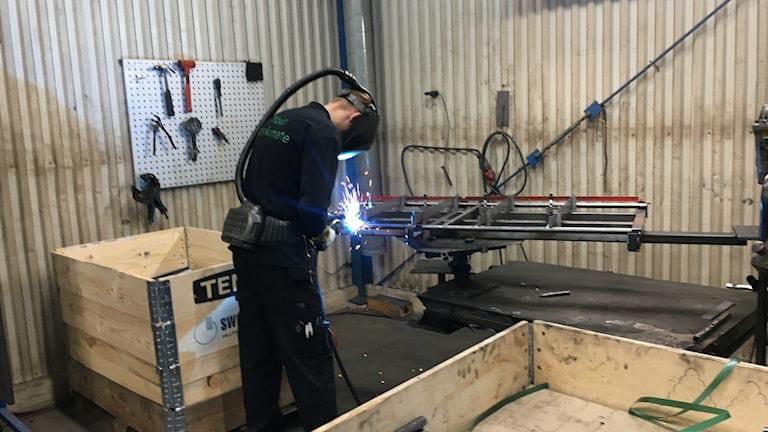 Man welding in a workshop.