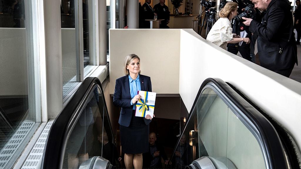A woman ascending an escalator holding a binder