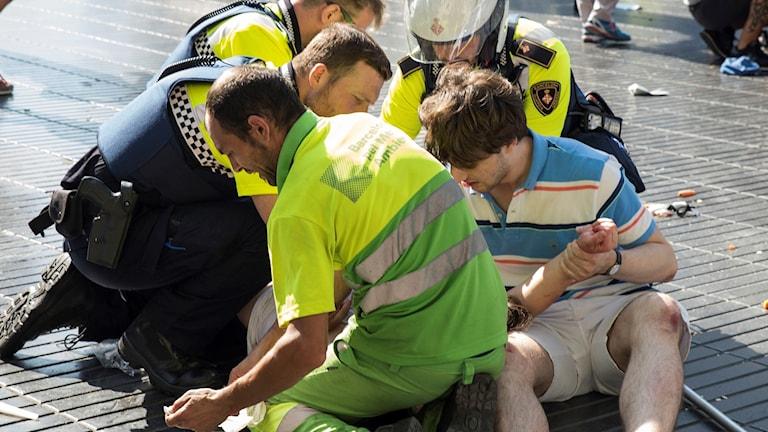 Spanish policemen help someone injured in the attack.