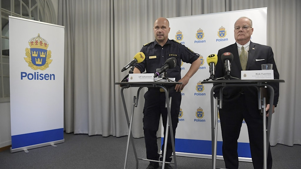 Two men behind microphones, next to the logo of Swedish police.