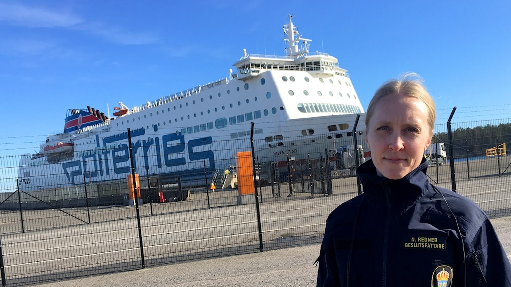 A woman standing outside with a large ferry in the background.