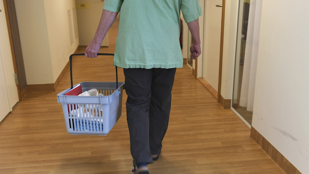 A person wearing green uniform carrying a basket in an old people's home.