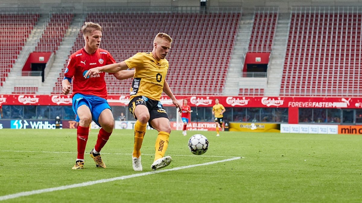 Two footballers in a match, with empty stands behind them.