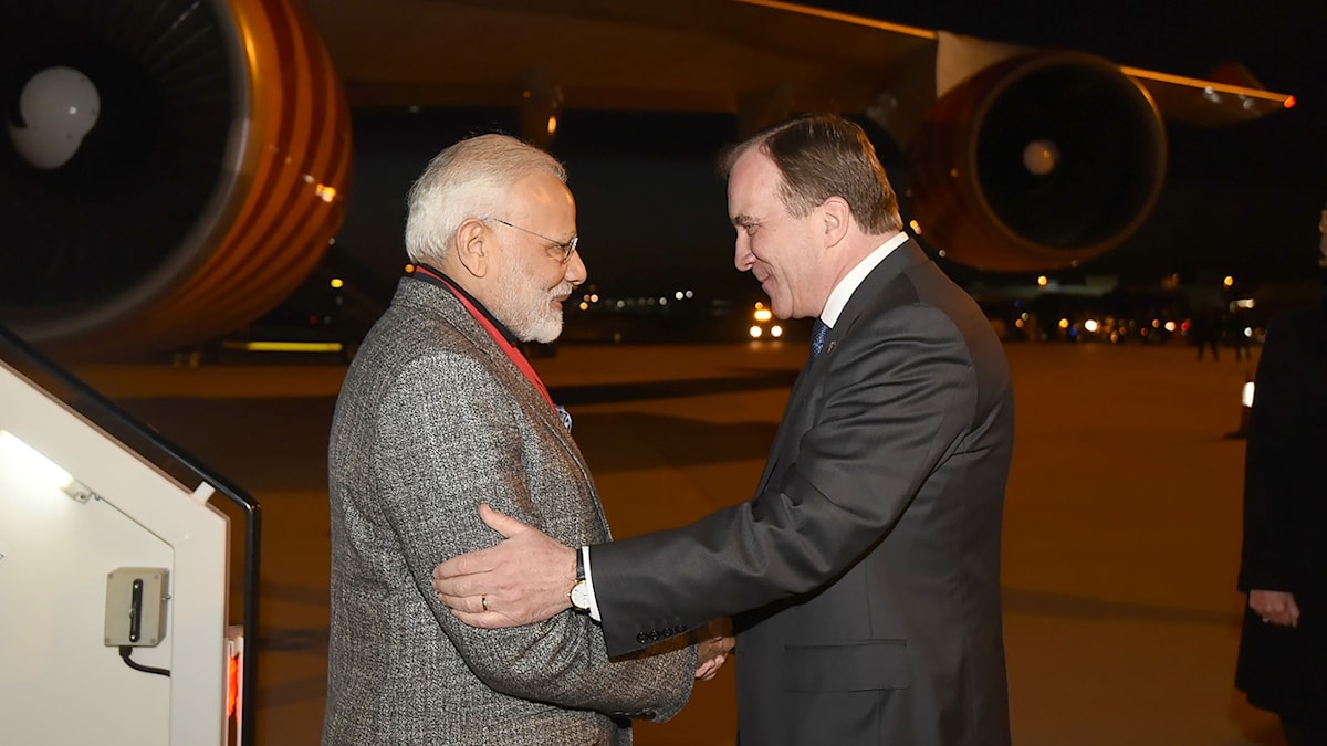 Two men shaking hands next to an airplane, at night-time.