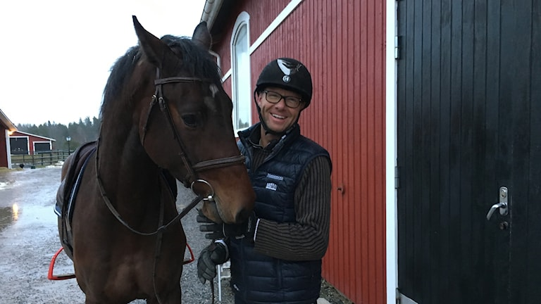 Man, smiling at the camera, in a riding helmet, with a horse in the reigns.