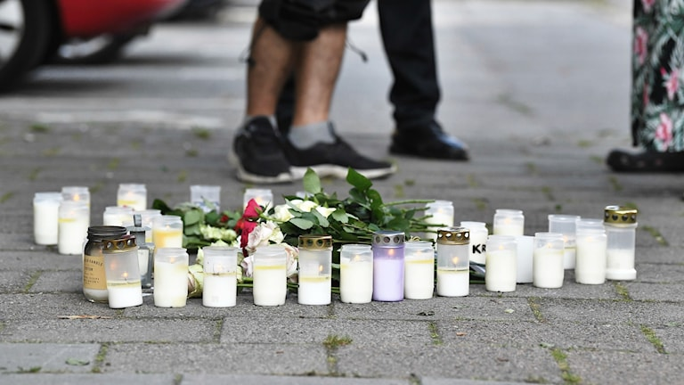 Candles and flowers on the ground. People standing nearby.
