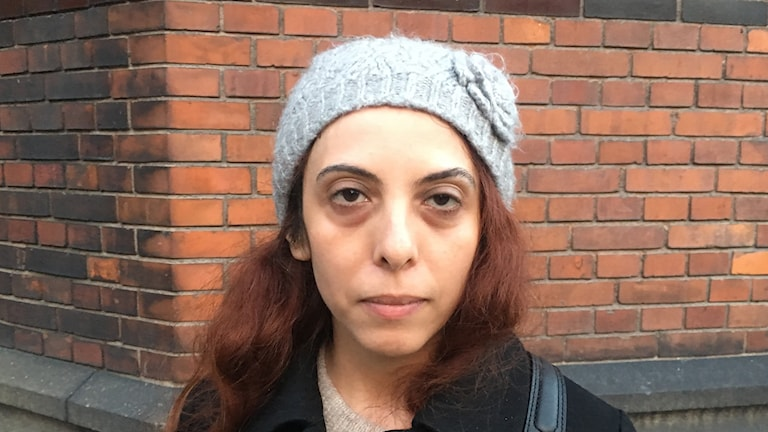 Portrait of a woman, with black bags under her eyes.