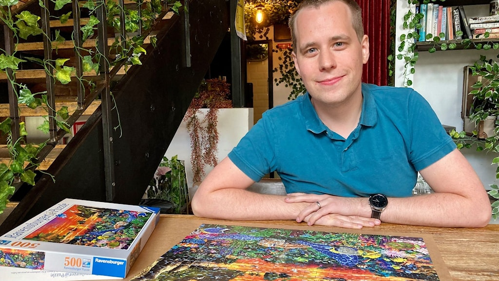 A man rests his arms on a table with a colorful jigsaw puzzle on it.