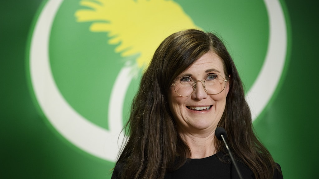 A woman with long dark hair and glasses in front of the logo for the Swedish Green Party.