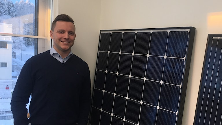 A man standing next to a solar panel.
