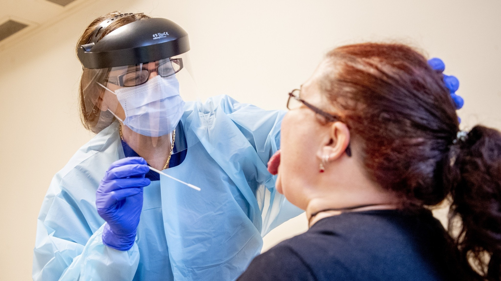 An image of a health care worker in PPE holding a swab above a woman's head.