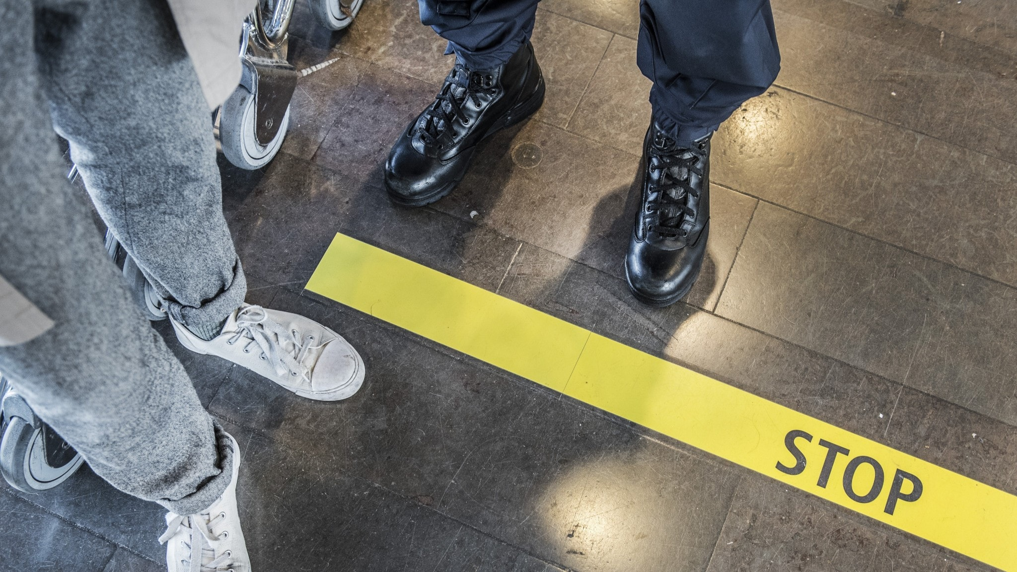"A passport queue at Arlanda airport showing a line on the floor with the word ""stop"""