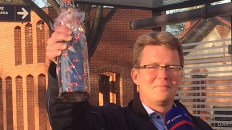Commuter lobbyist Michael Randropp raises a champagne bottle to celebrate the end of ID checks.