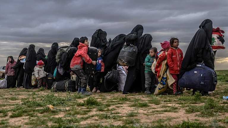 Women and children lined up in a field.