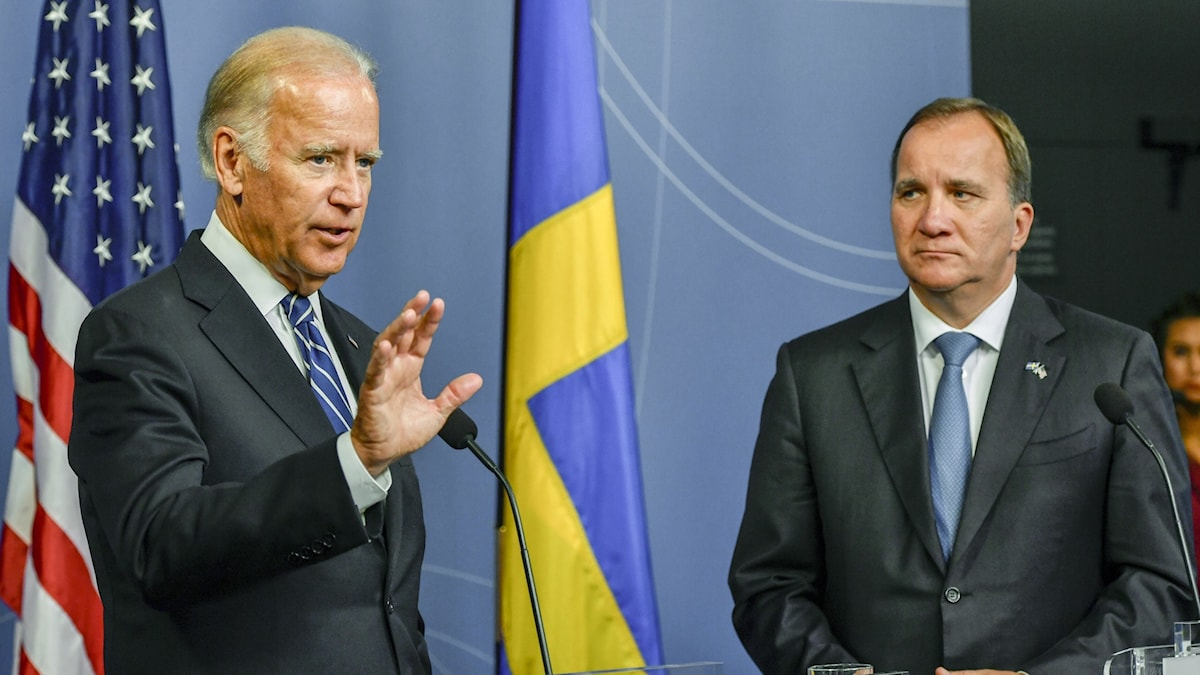 Two men at a press conference with US and Swedish flags