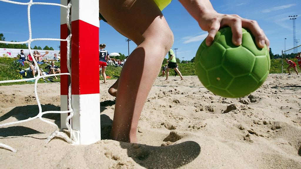En person står i sanden och håller i en grön handboll.