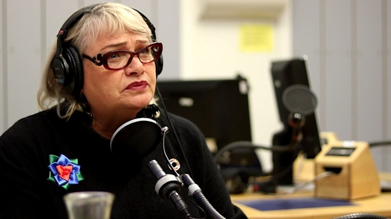 A woman with glasses wearing headphones in front of a microphone.